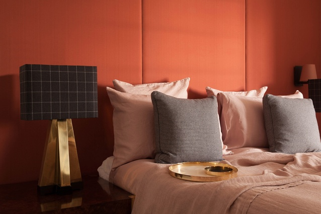 Custom panelled upholstered headboard in salmon cantaloupe, 1970s vintage lamps with cashmere wool shades, washed blush linen bedding with custom wool cushions.
