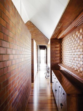 On the entry level, brick courses are opened to make screens for a breezeway that buffers and extends into the main bedroom.