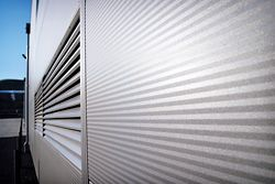 Detail of a typical exterior using Kingspan Insulated Architectural Wall Panel in micro-rib profile (KS1000 AWP).  Each panel  has an outer steel face, an internal steel liner, and high-performance, fire-resistant, thermal insulating infill. Advanced interlocking and fixing methods ensure weather-tightness  and an appealing exterior finish.