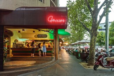 """The neon """"grocer"""" sign is in the architect's handwriting."""