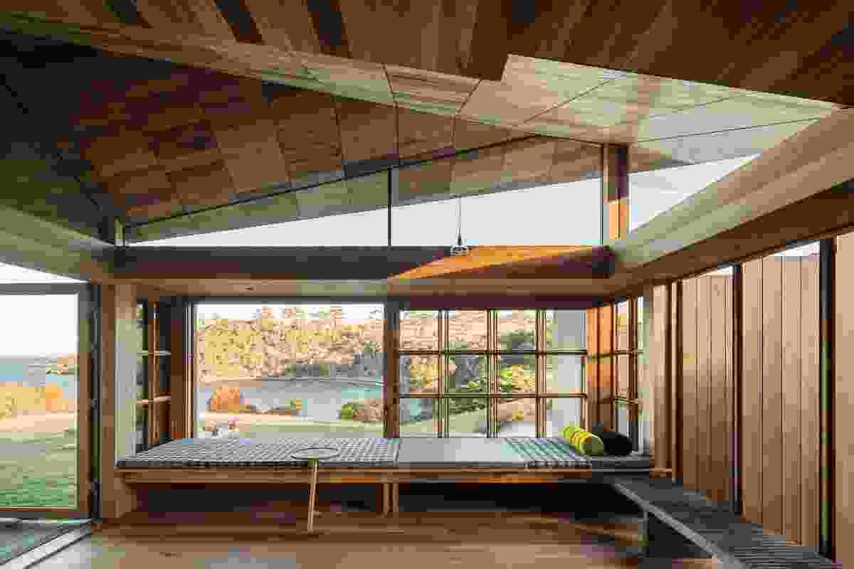 "In the living room, a window seat looks over the ""blessed ancient landscape"" through broad, multipaned windows that can completely slide away."
