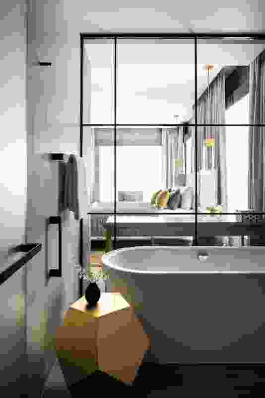 The use of glass walls in the bathroom helps to maximize usable space and diffuse natural light.