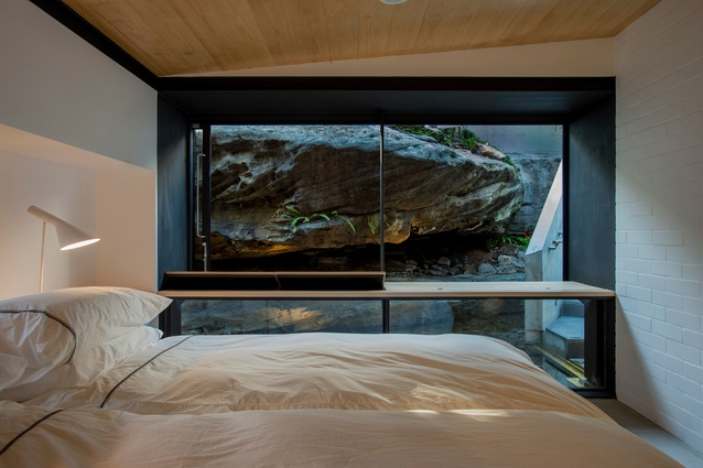 The main bedroom of the Donaldson House by Glenn Murcutt features a large glass wall facing the sandstone shelf.