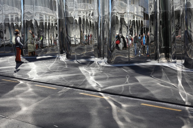The facade's highly reflective surface creates moving shadows over the street.