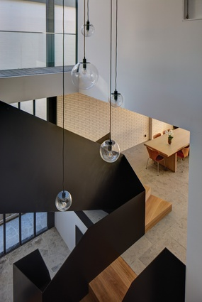 An internal void housing the sculptural central stairway dramatically splits North Bondi House in two.