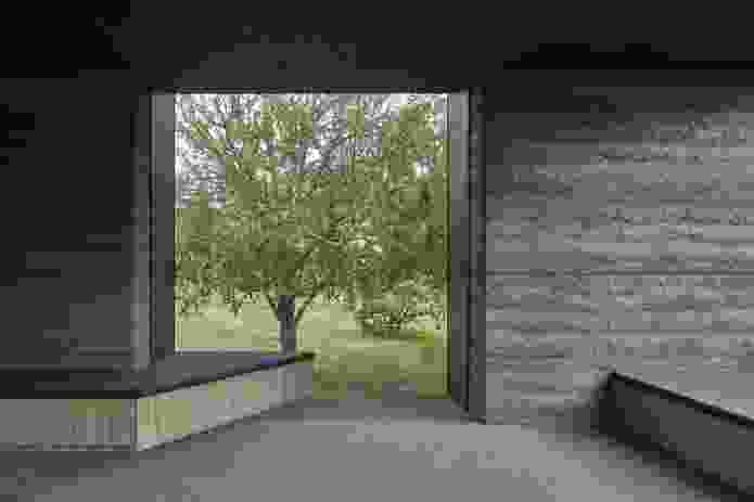 A window on the southern side of the home incorporates built-in seating facing the trees.
