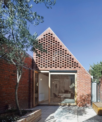 A lattice wall, made of reclaimed bricks from the demolished rear, shades the western edge.