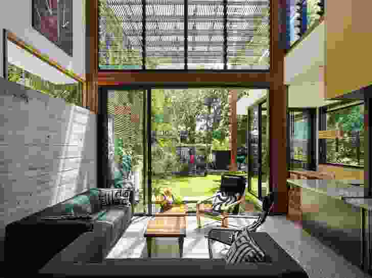 The garden room opens to the outdoors, visually linked by the rough concrete wall.
