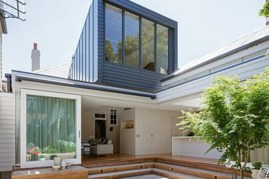 The rear of the home opens out to a planted courtyard, with the box-like addition casting a watchful eye overhead.