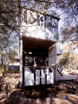 North-east elevation, with the balcony off the study below. Here the containers' end doors are reused structural blinkers, while removed side walling becomes balustrading.Images: Peter Bennetts