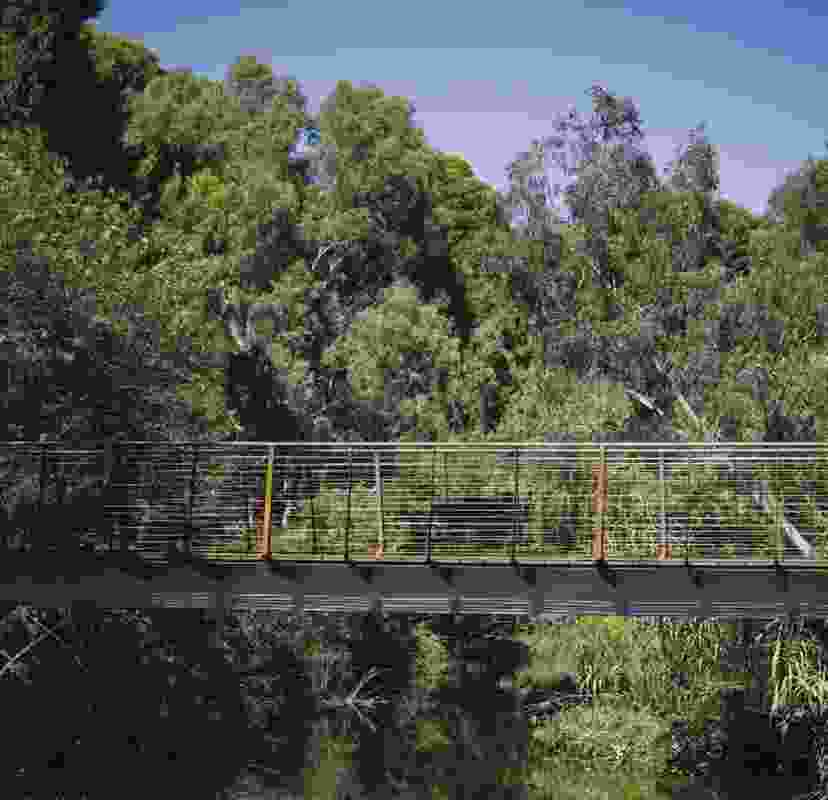 The bridge is positioned midway down the embankment, forming a closeness to the water.