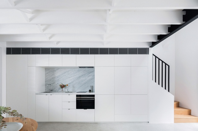 The kitchen, laundry, TV, storage space, stairs and bathroom all interlock within a compact service spine.