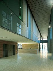 """The travertine and timber-clad double-height boulevard, with colourback glass """"bar"""", runs the length of the site. The reception desk is seen in the middle ground."""