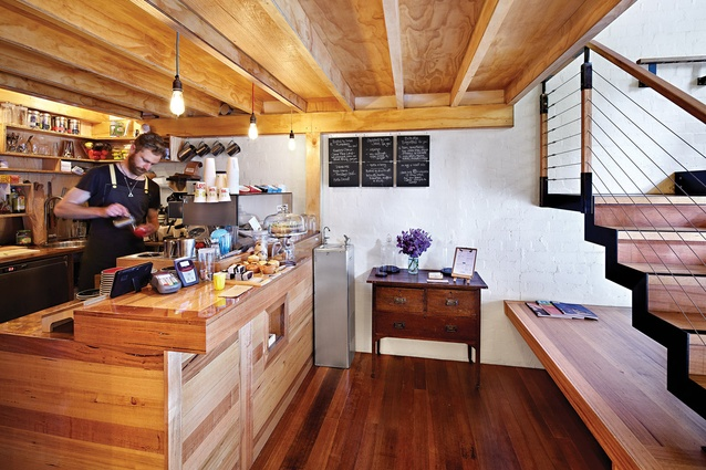 The coffee bar, located at the back of the cafe, is framed in plywood.