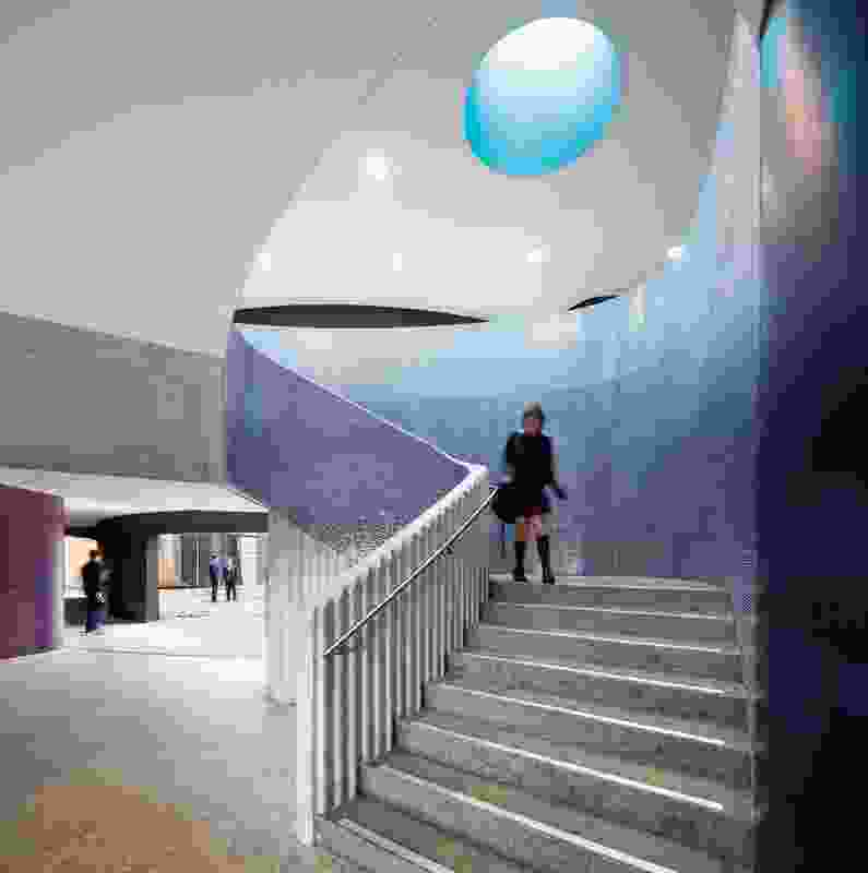 A curved concrete staircase lined in blue mosaic tiles.