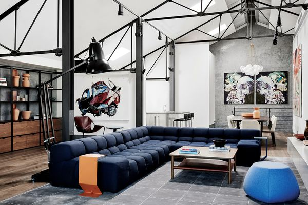 Beneath the warehouse's steel trusses, over-scaled furniture gives structure to the open-plan living area.