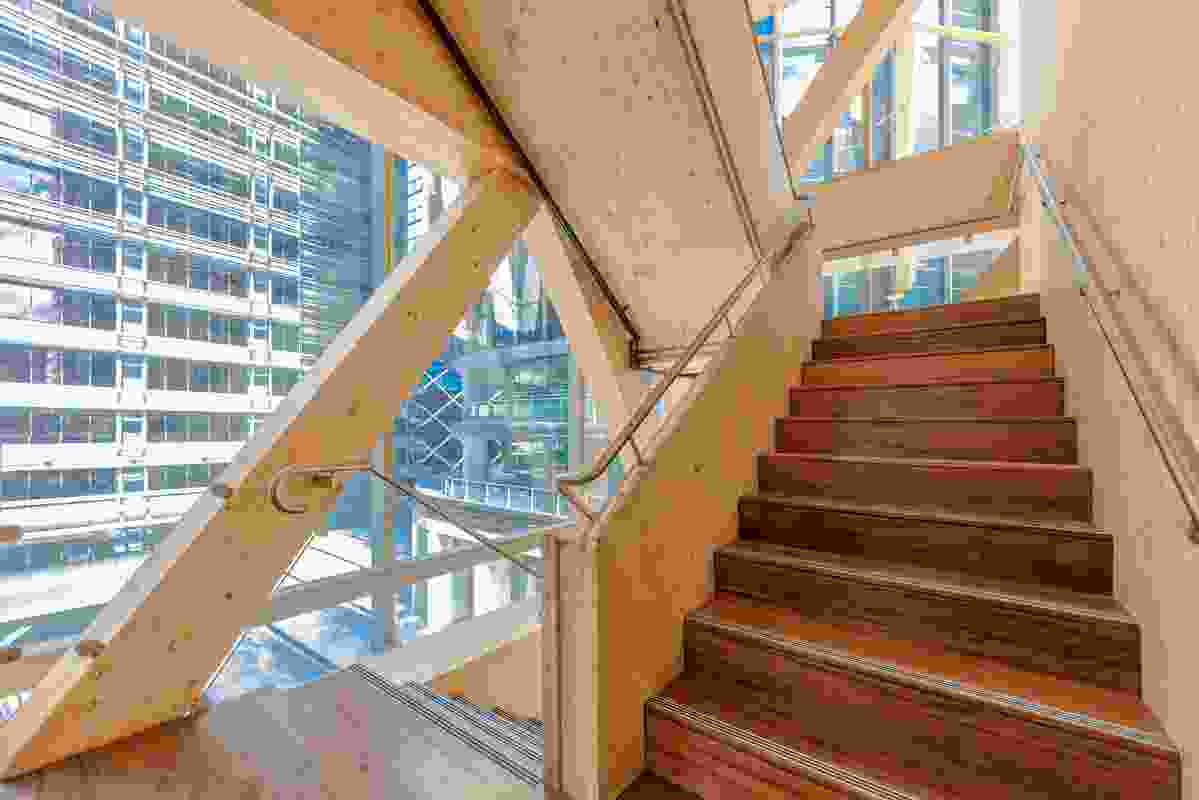 The building's fire stairs are enclosed with fire-rated glass, welcoming light and views and encouraging circulation between floors.