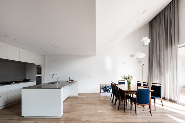 The kitchen is tucked beneath the canopy of the existing ceiling, a more modest, cosy space than the new volume.