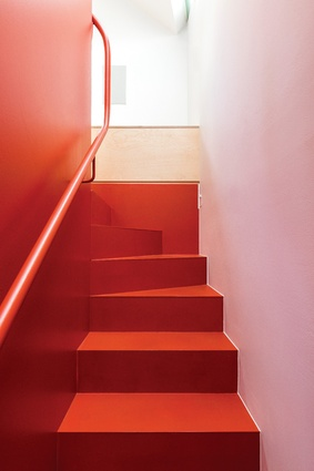 Painted in a deep burnt red, the stairs play an important role in visually and structurally anchoring the studio.