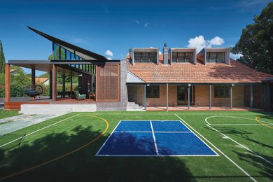 The home borrows shade and a connection with nature from a park to the corner of the site, on the other side of the private tennis court.