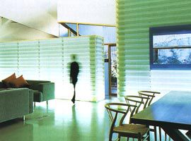 Looking across the living and dining areas to the translucent glowing storage and kitchen boxes. The bedroom courtyard is beyond.