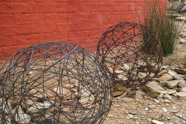 Old fencing wire used for sculptures in front of mudbrick wall.