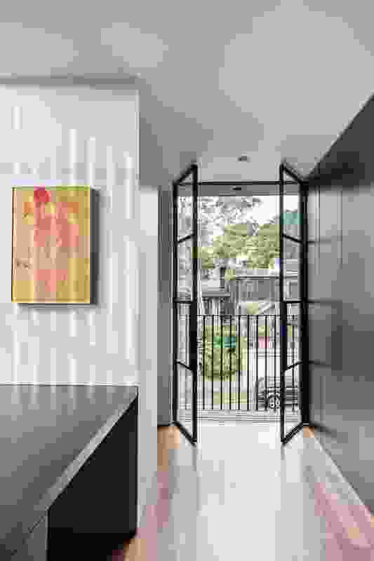 Black joinery, windows, doors and finishes provide consistency and anchor the space. Artwork: John Reid.