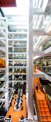 Open and light, the central atrium is traversed by a bold orange stair.