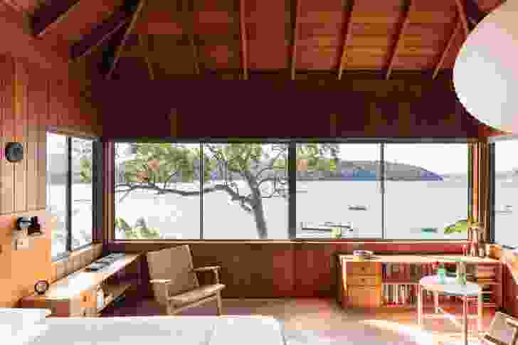 The main bedroom, under a steeply pitched roof, offers views north up the Pittwater to Barrenjoey Lighthouse.