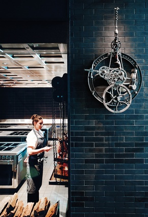 A steampunk-like artwork of slow-turning cogs and chains is powered by the kitchen's rotisserie. Artist: Robert Higgs.