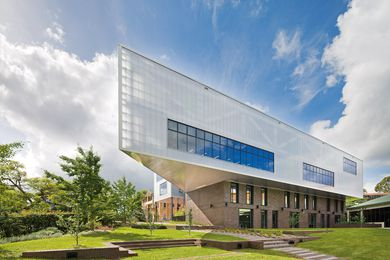 The two-storey polycarbonate-clad volume containing a learning centre cantilevers over a manganese brick base.