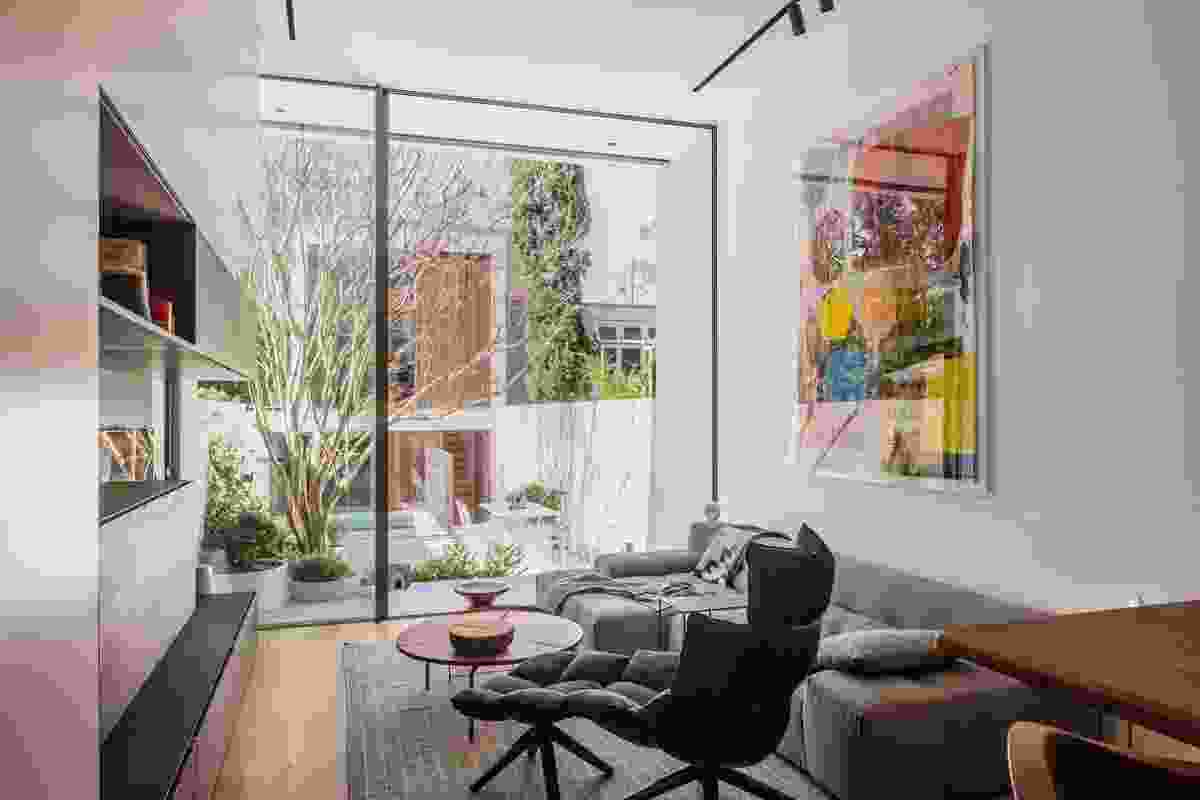 The house opens onto an elegantly designed courtyard with a garage and studio beyond. Artwork: Linus Bill and Adrien Horni.