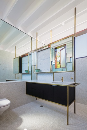 The brass-framed bathroom joinery is designed as a piece of furniture.