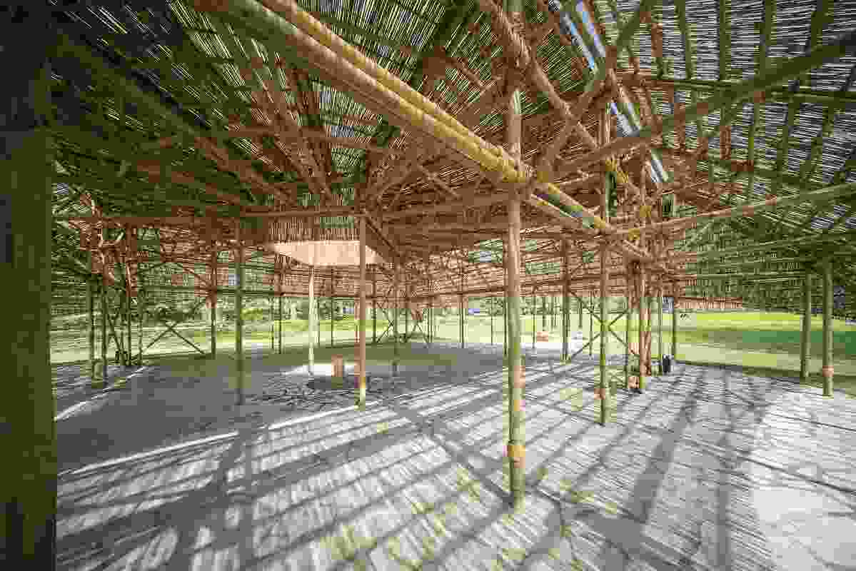 The pavilion is supported by a lattice-like bamboo structure.