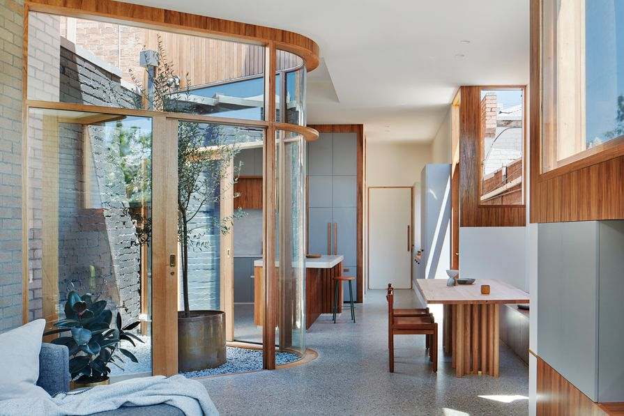 A curvilinear, triangular courtyard separates the kitchen and living areas and draws light into the depth of the plan