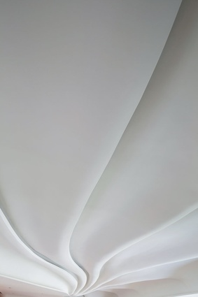 The undulating ceiling conceals deep concrete beams typical of Hong Kong apartments.