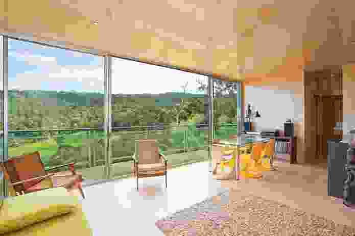 The living area is privy to a distant view framed by a canopy of gum trees.