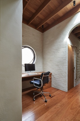 A circular pivot window in the study sits in conversation with the arched doorway.