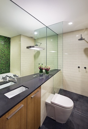 The main bathroom includes a feature wall of green mosaic tiles.