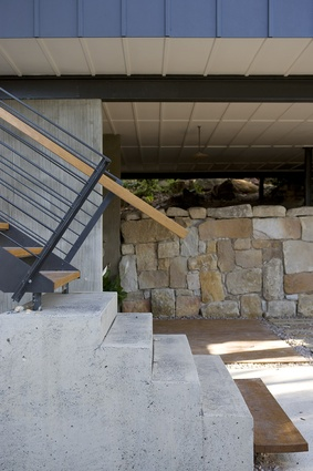 On the ground floor, broomed concrete walls form a solid base housing the garage and laundry.