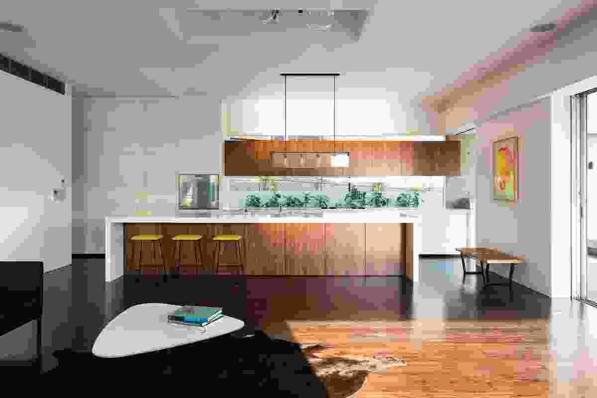 The kitchen keeps to the dark timber palette. Artwork: Kate Banazi.