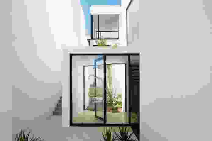The setback zones allow light and air to enter along the side of each house and an external stair that runs past a sunken garden connects the front and rear of each lot.