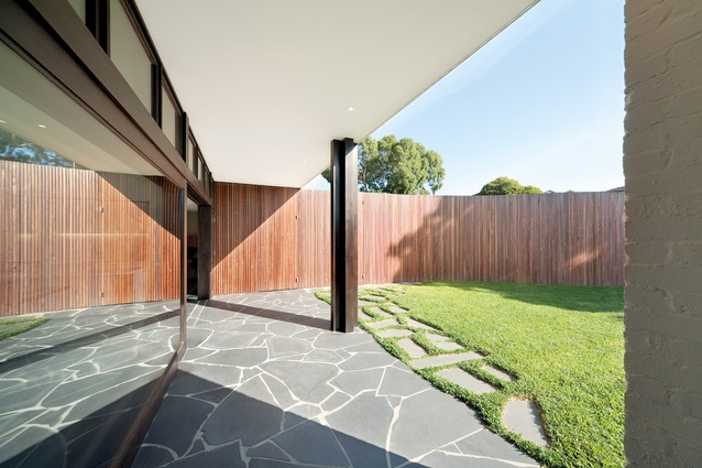 A crazy-paved floor flows from indoors to the outdoor terrace, before breaking up as it enters the lawn.