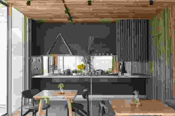 In the Salon, the kitchen is tucked behind a timber screen, seen here on the right. A breakfast of local produce is served on the adjacent bench.