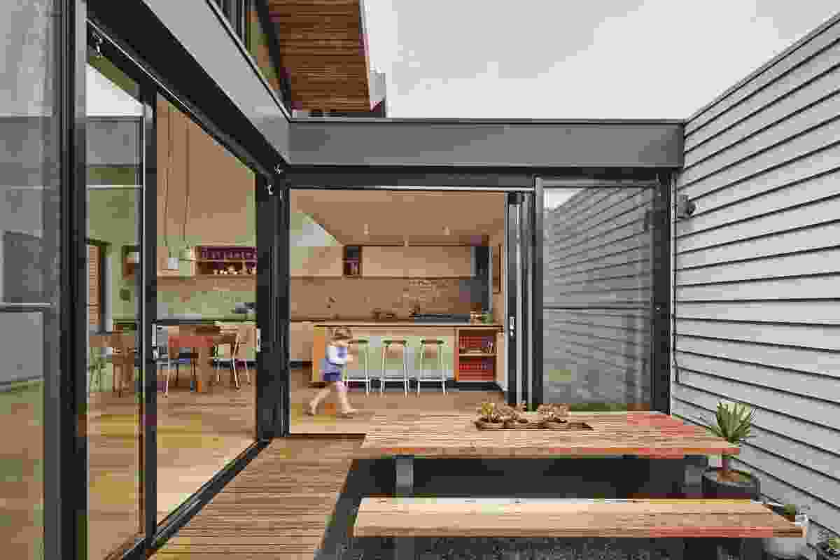 The lowered courtyard, carved out of the addition, has decking that doubles as seating.