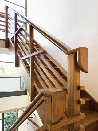 A central stair crafted from blackbutt timber complements the tones of the ochre- tinted plaster walls.