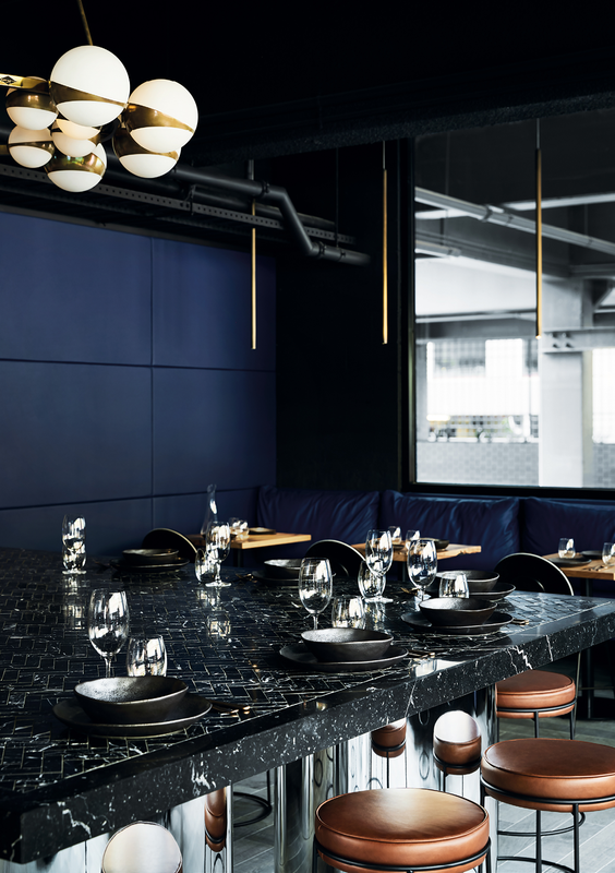 A generous communal table topped with nero marquina herringbone tiles anchors the open-plan space, drawing visitors to congregate centrally.