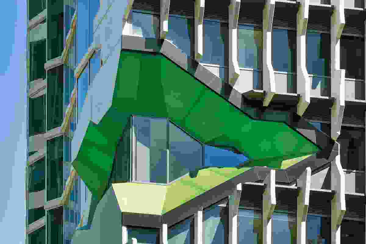 A series of openings clad in green panels disrupt the order of the concrete fins on the facade, revealing the inner workings of the Institute.