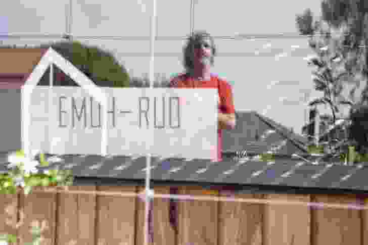 """A sign saying """"emoh-ruo"""" sits in the window of Peter and Mum's residence."""