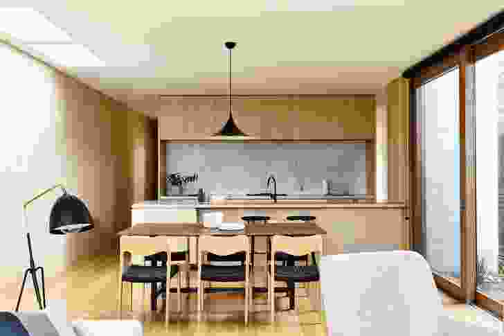Full-height joinery is hidden around an alcove, maximizing the perceived width of the kitchen.